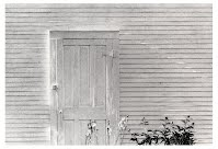 AGAIN, SPRING by Carroll Jones III...white building w/door rimmed in bright sunlight, iris flowers