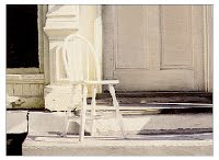 SEPTEMBER SETTING by Carroll Jones III oil painting, white chair on porch of old commercial building, also white.